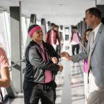 Superintendent and alum Nathan Quesnel greets a student in the East Hartford High hallway.